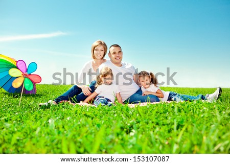 Happy family together in outdoor park  at sunny day. Mom, dad and two daughters in the  green garden.  Group of people on green grass - stock photo