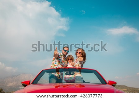 Happy family travel by car in the mountains. People having fun in red cabriolet. Summer vacation concept - stock photo