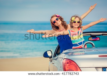 Happy family travel by car to the sea. Woman and child having fun in cabriolet. Summer vacation concept - stock photo