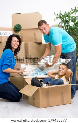 happy family unpacking boxes and moving into a new home - stock photo