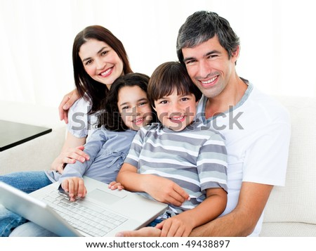 Happy family using a laptop sitting on sofa at home - stock photo