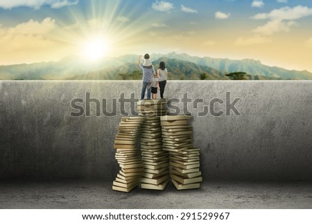 Happy family using a pile of books to climb a wall and look at the mountain view - stock photo