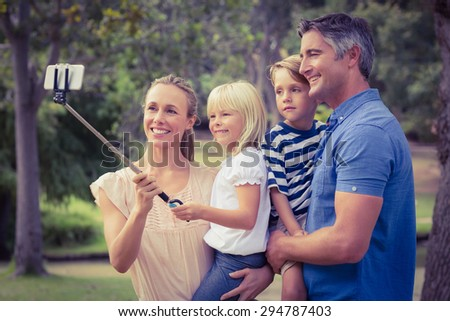 Happy family using a selfie stick in the park on a sunny day - stock photo