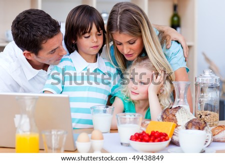 Happy family using laptop during the breakfast in the kitchen - stock photo