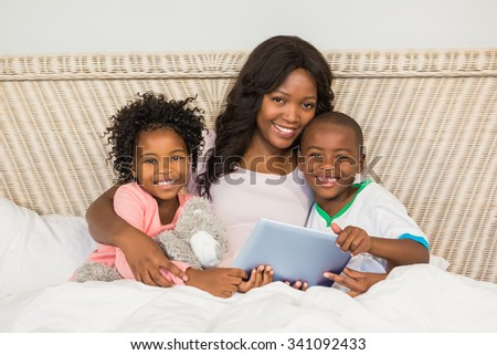 Happy family using tablet in bed at home - stock photo