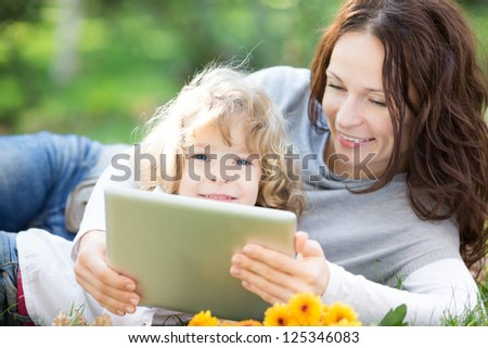 Happy family using tablet PC against green spring background - stock photo