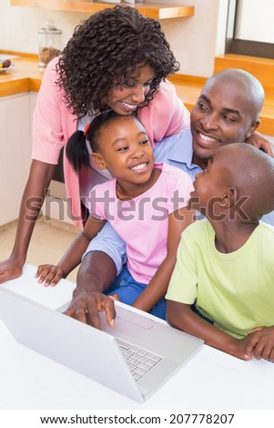 Happy family using the laptop together at home in the kitchen - stock photo