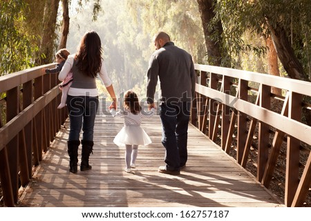 Happy family walking away towards a forest on an old wooden bridge - mother, father, two daughters - stock photo