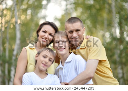 Happy family walking in a birch forest - stock photo
