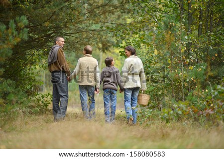 Happy family walking in the  forest - stock photo