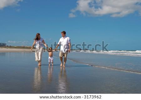 Happy family walking on a beach - stock photo