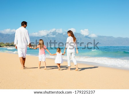 Happy family walking on the beach - stock photo