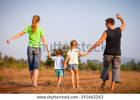 happy family walking on the road - stock photo