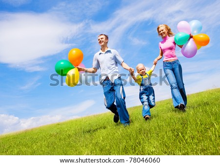 happy family walking with balloons outdoor on a warm summer day - stock photo