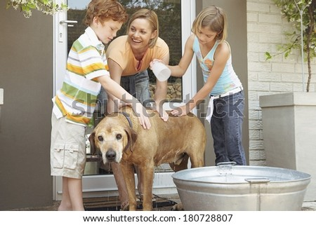 Happy family washing their dog - stock photo