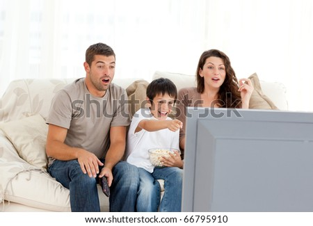 Happy family watching a movie on television together on the sofa at home - stock photo