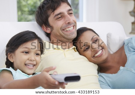 Happy family watching television together on the sofa - stock photo