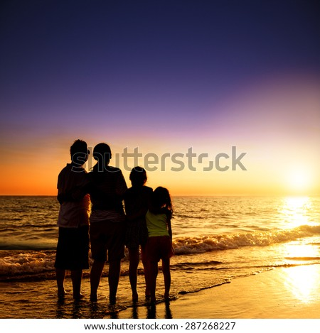 happy family watching the sunset on the beach - stock photo