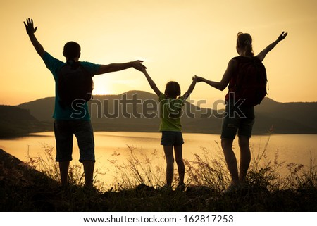 Happy family watching the sunset on the lake - stock photo