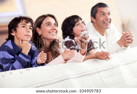 Happy family watching tv together and lying in bed - stock photo