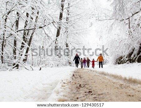 Happy family winter fun outdoors. Active parents with kids running in snowy forest - stock photo