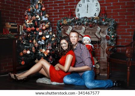 Happy family with a child celebrates Christmas - stock photo