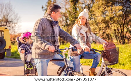 Happy family with a little daughter sitting on a bike seat riding bicycles by the nature on a sunny winter day - stock photo