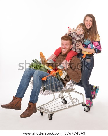 Happy family with a shopping cart isolated over white. Handsome man lying in shopping cart with groceries. - stock photo