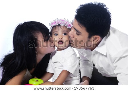 Happy family with Asian parents kissing their baby girl isolated over white - stock photo