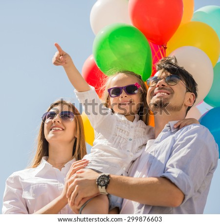 Happy family with balloons looking up outdoor on a summer day, daughter pointing at the top. - stock photo