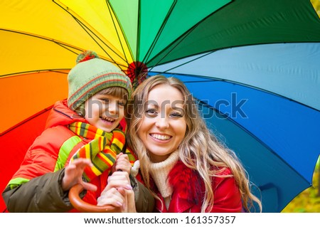 Happy family with bright multicolored umbrella in autumn park - stock photo