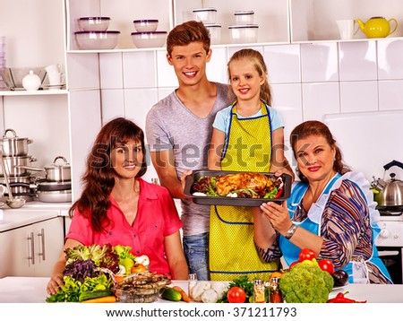 Happy family with child and grandmother cooking chicken at kitchen.  - stock photo