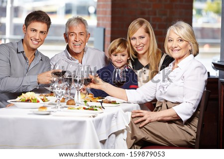 Happy family with child clinking glasses in a restaurant - stock photo