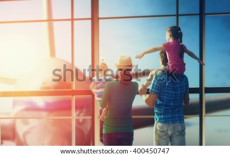 Happy family with children at the airport. Parents and their children look out the window at the plane. - stock photo