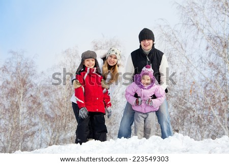 Happy family with children in winter park - stock photo