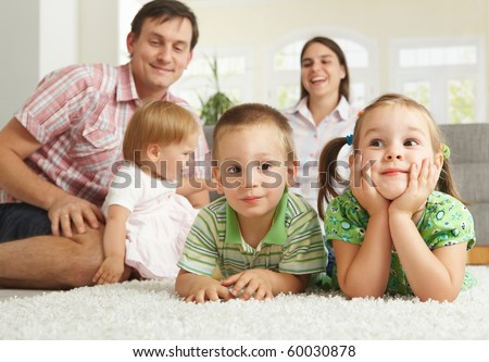 Happy family with 3 children sitting on floor of living room at home.? - stock photo