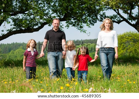 Happy family with Children walking down a meadow with dandelion flowers at a bright spring day - stock photo
