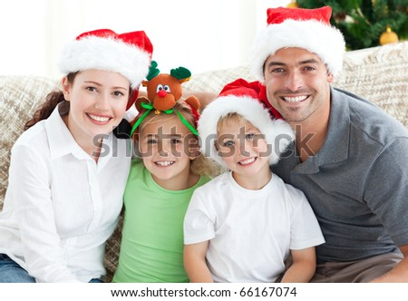 Happy family with Christmas hats sitting on the sofa at home - stock photo