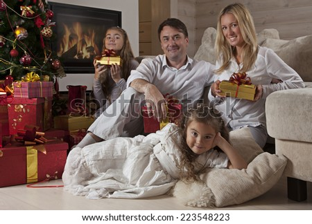 Happy Family with Christmas Presents In Front Of Decorated Tree At Home  - stock photo