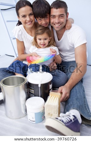Happy family with color samples to paint new house - stock photo