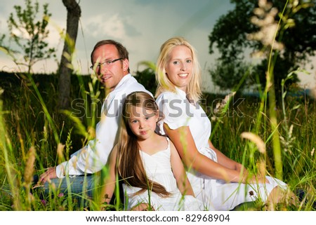 Happy family with daughter girl sitting in a meadow in summer before a thunder storm - stock photo