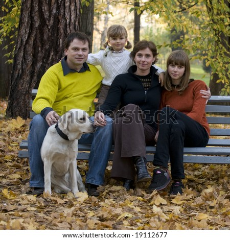 Happy family with dog at autumn time - stock photo