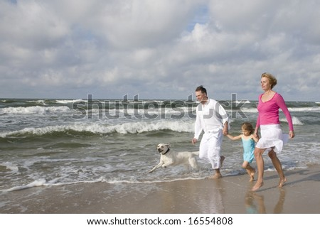 Happy family with dog on the beach - stock photo