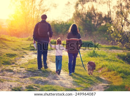 Happy family with dog walking in the village at sunset  back to camera - stock photo