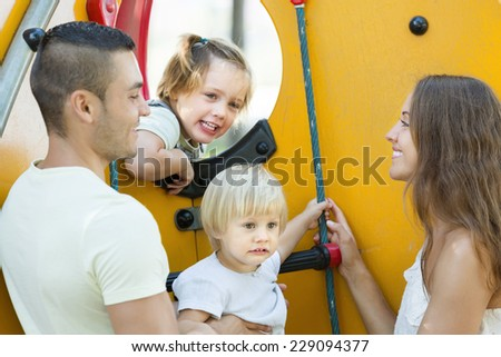 Happy family with kids at playground's stairs outdoors - stock photo