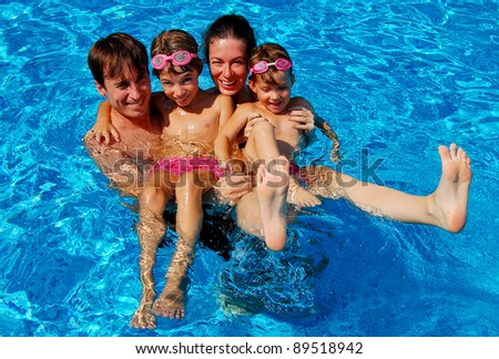 Happy family with kids having fun in swimming pool. Smiling parents and children on summer vacation - stock photo