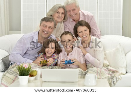 Happy family with kids with laptop - stock photo