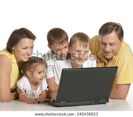 Happy family with laptop on a floor - stock photo
