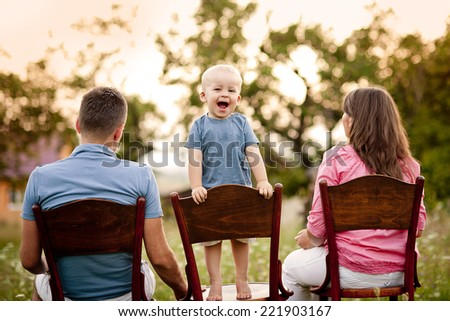Happy family with little boy sitting on chairs in the meadow - stock photo
