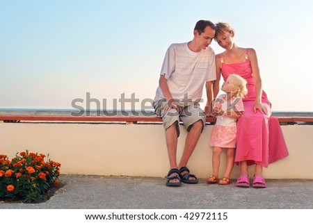 Happy family with little sitting on bench on resort - stock photo